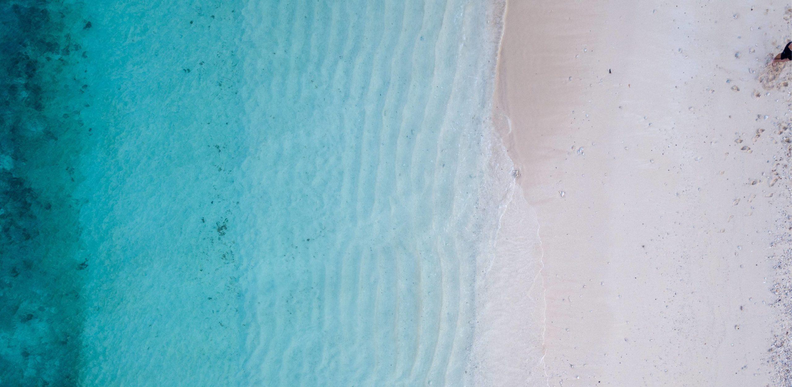 Lava Shell Massage - mit blick von oben auf einen Strand mit Wasser